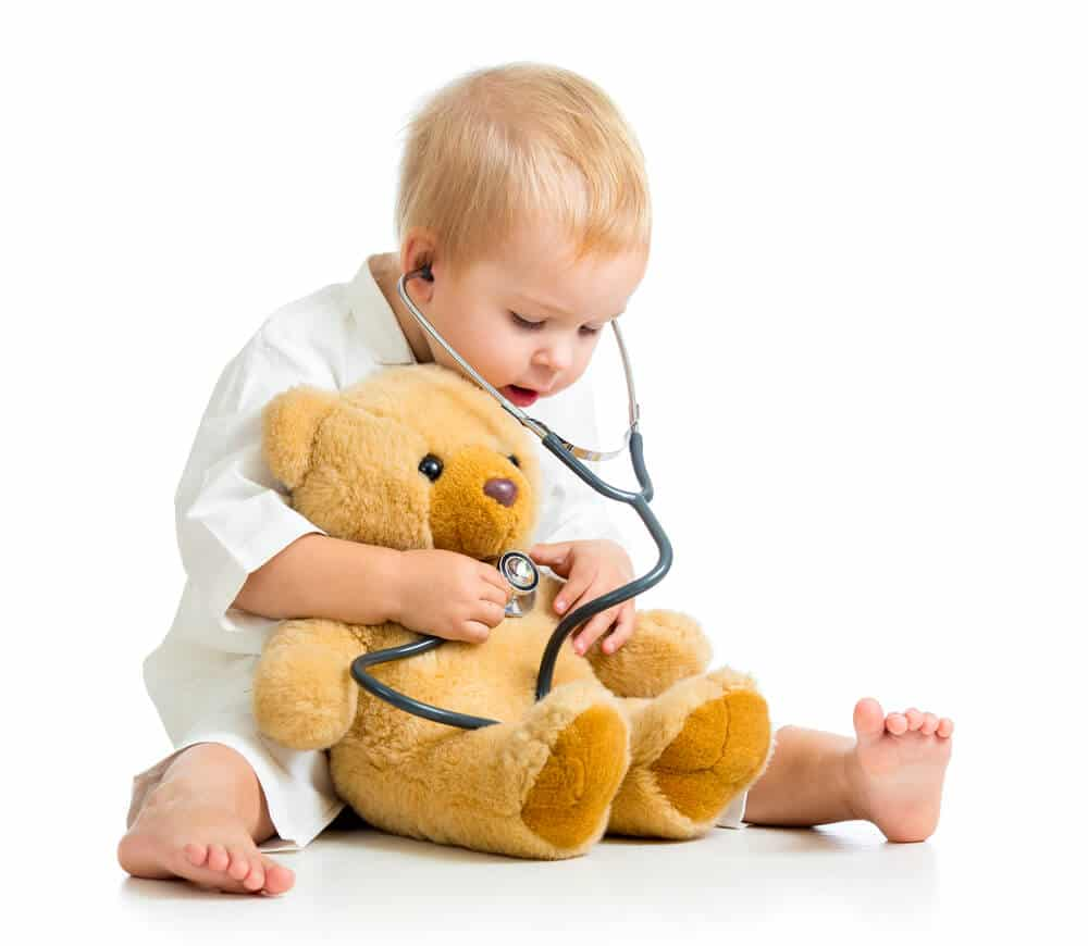 Adorable child in clothes of a doctor with a teddy bear
