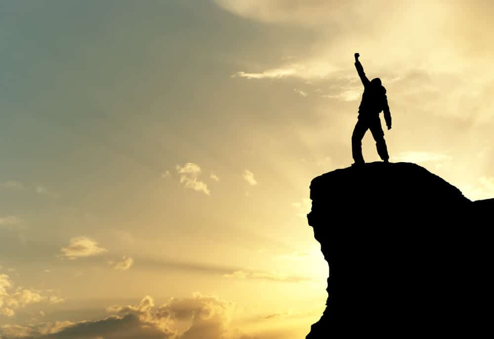 Man on top of mountain proud of his achievement
