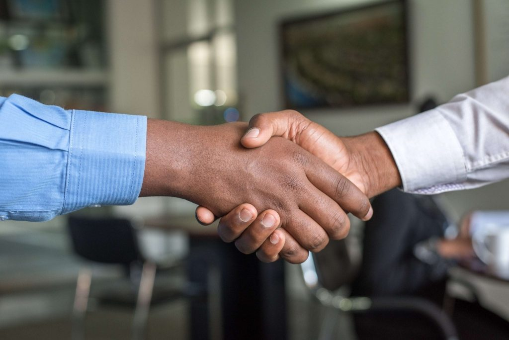 Two African-American men shaking hands after a successful job interview