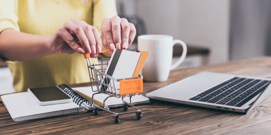 woman pushing a toy trolley filled with credit cards on her desk symbolizing the shift to online shopping as the new norm in the retail industry