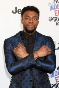 Chadwick Boseman standing with purpose doing the Wakanda sign