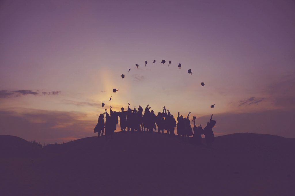 Silhouette of fresh graduates throwing their hats into the air simbolizing hope for comfortably landing a job