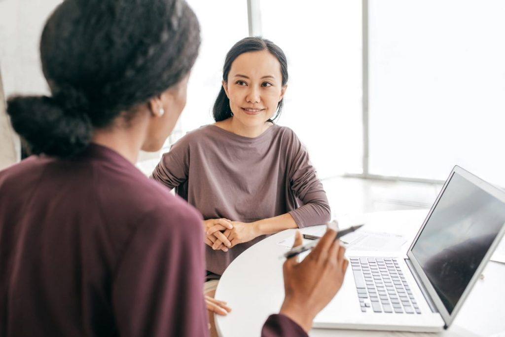 Asian woman smiling at a black woman while getting feedback on her resume