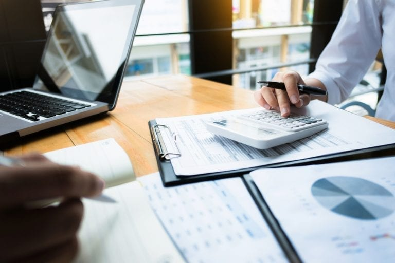 close-up image of financial documents and a calculator on a table while two accountants look over them