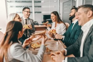 Colleagues laughing while eating lunch in the office and getting to know an employees who just started working at the company