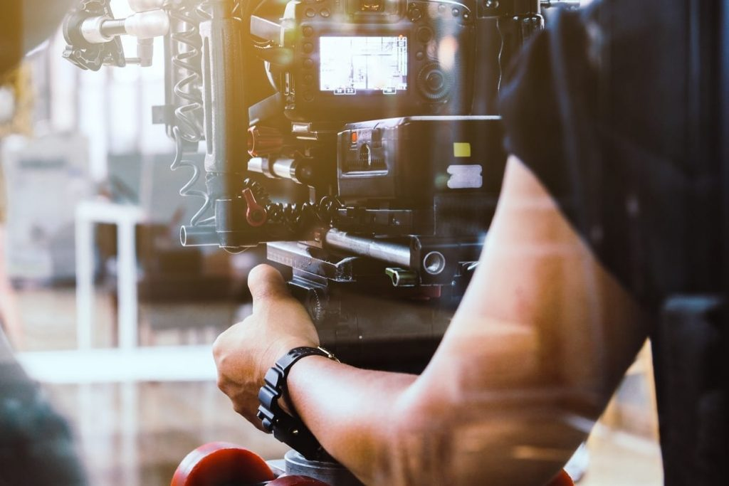 Close-up photo of high-end camera equipment being manned by an unrecognizable cameraman while working in the entertainment industry