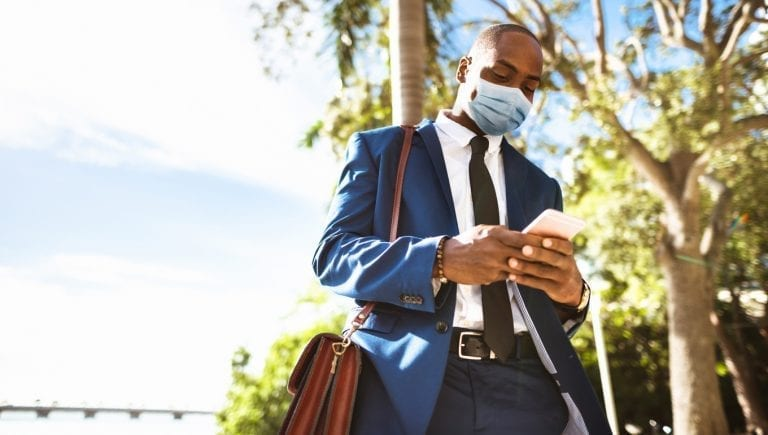 african-american man in a blue suit wearing a mask while using his phone outside in miami