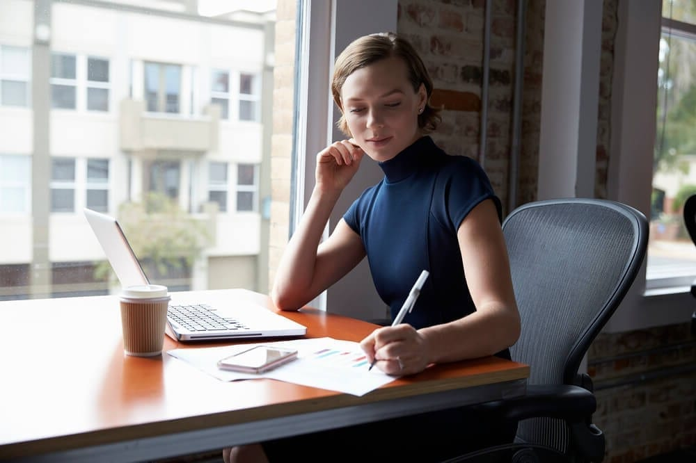 Businesswoman making notes during a remote employee onboarding process
