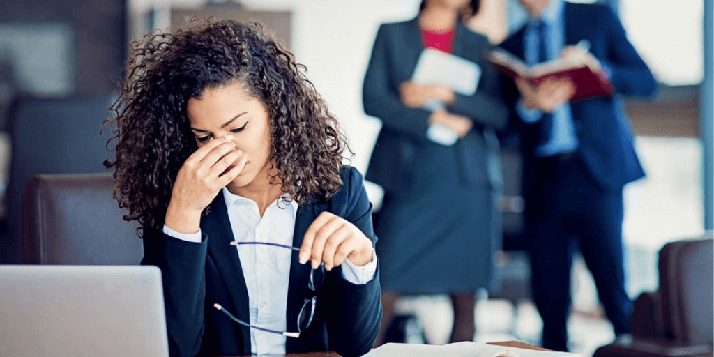 Woman employee stressed out from being bullied at work.