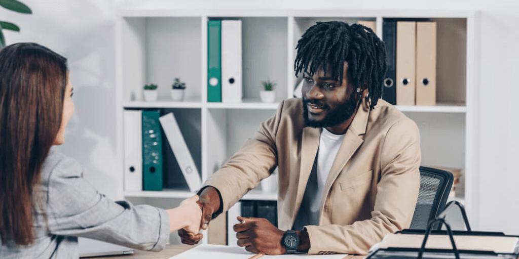African-american hiring manager shaking hands with a woman after a successful second interview
