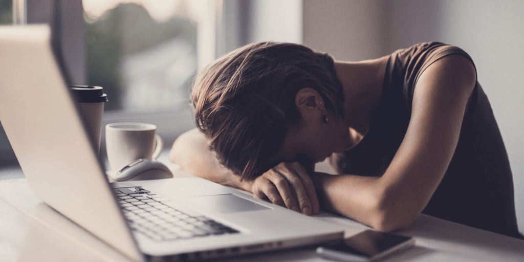 woman slumped over her desk while trying to survive a toxic workplace environment