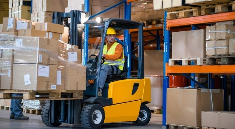 warehouse worker moving boxes with a forklift