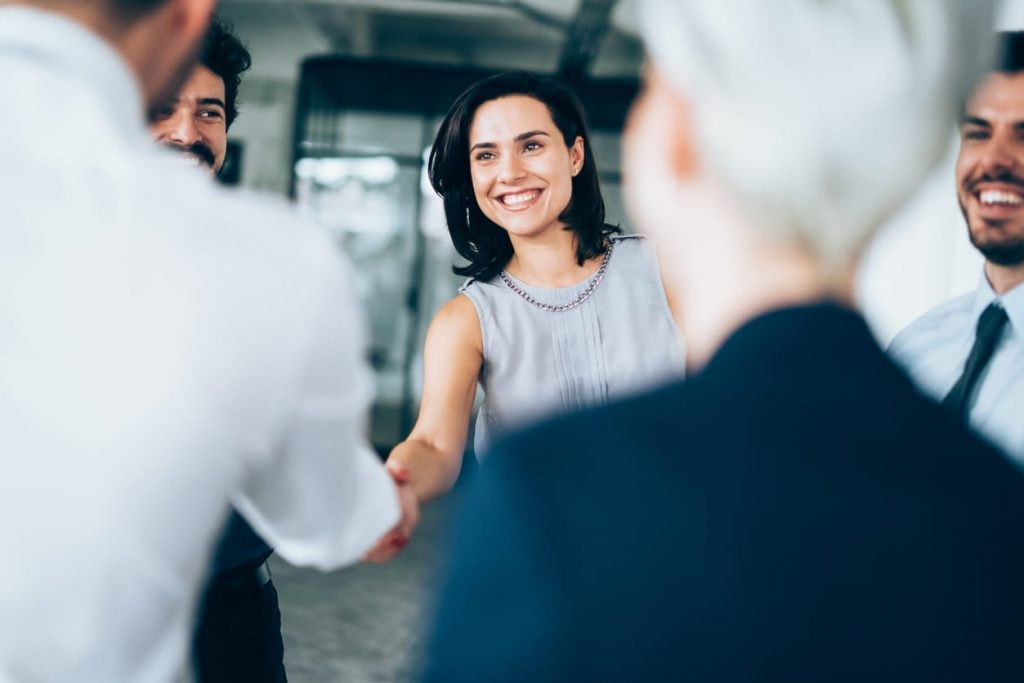 smiling woman shaking the hand of a male colleague