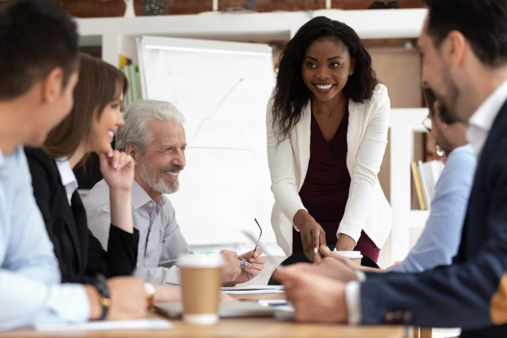 black woman smiling while presenting to a diverse group of coworkers