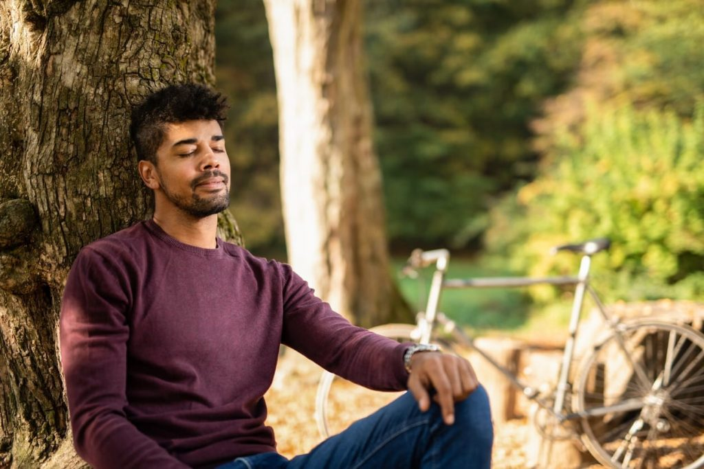bearded man meditating under a tree outdoors
