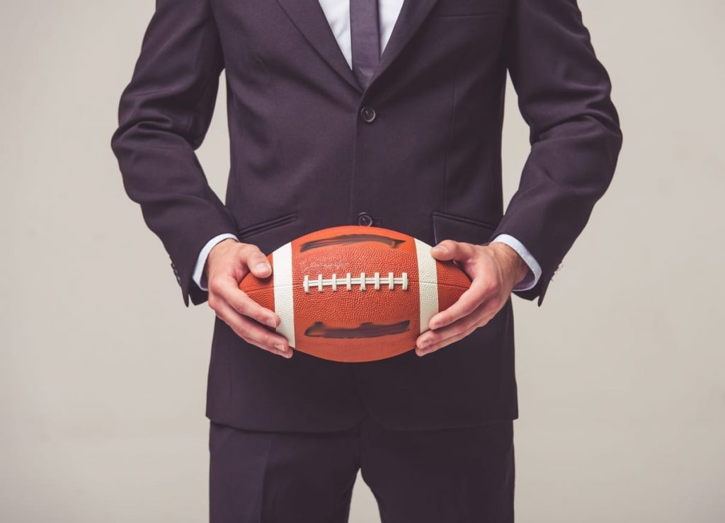 cropped image of a man in a business suit holding a football in detroit lions office