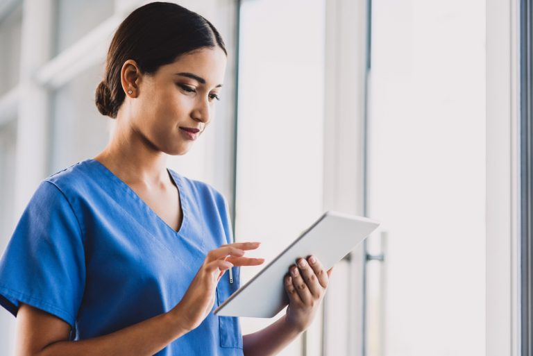a nurse social worker in blue scrubs using a tablet to check patient records
