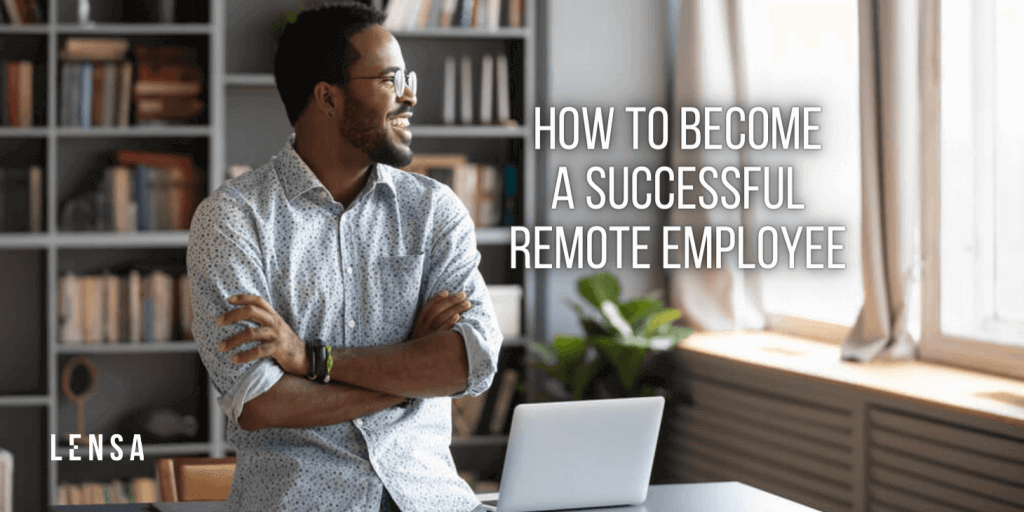 A happy and successful remote employee smiling at home while leaning on his desk
