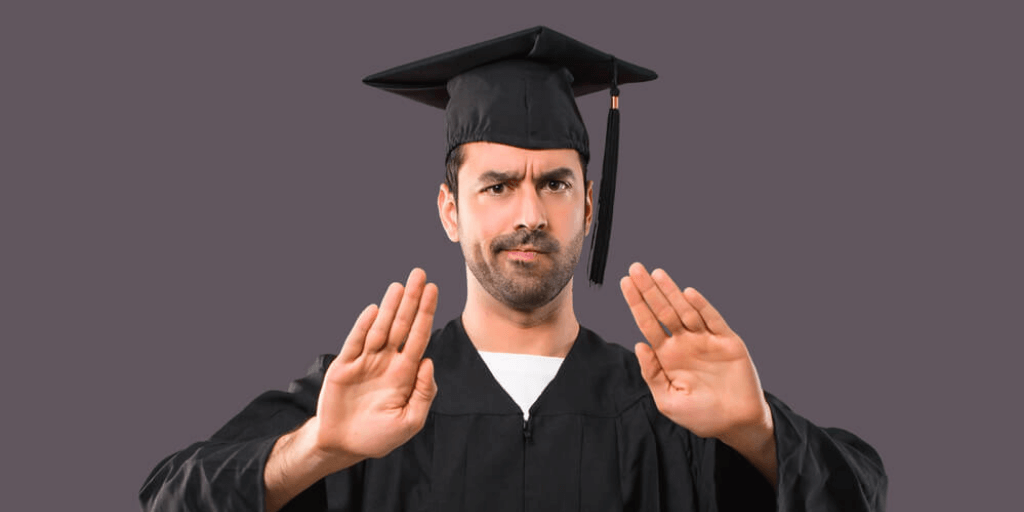 Successful man in a university cap and gown showing stop signs that symbolize high paying jobs that do not require a college degree