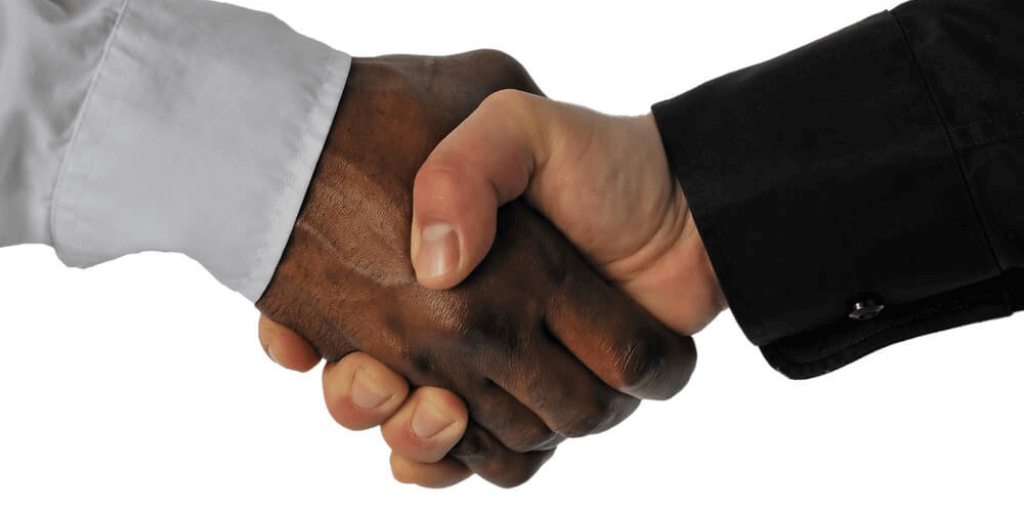 friendly handshake between a white and an african-american businessman as a sign to end racism in the workplace