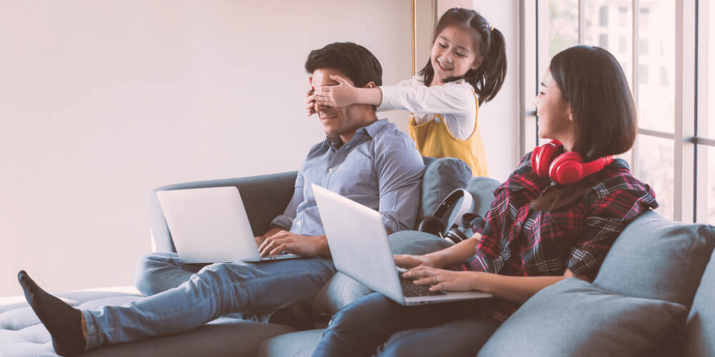 remote-based family working from their couch while raising their daughter
