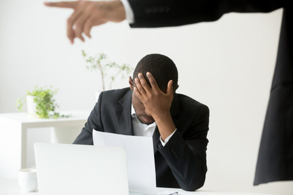Frustrated hopeless african-american office worker getting fired from job