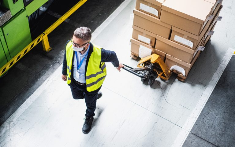 warehouse worker in a protective suit transporting packages in a warehouse