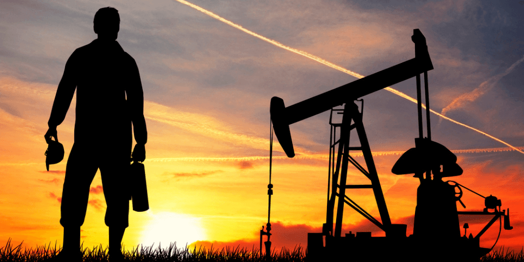 oil pump operator standing near an oil pump in the field at sunset