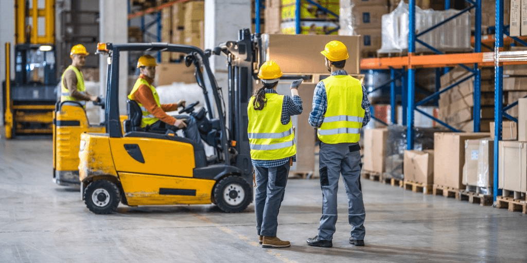 Warehouse workers working with forklifts in a warehouse