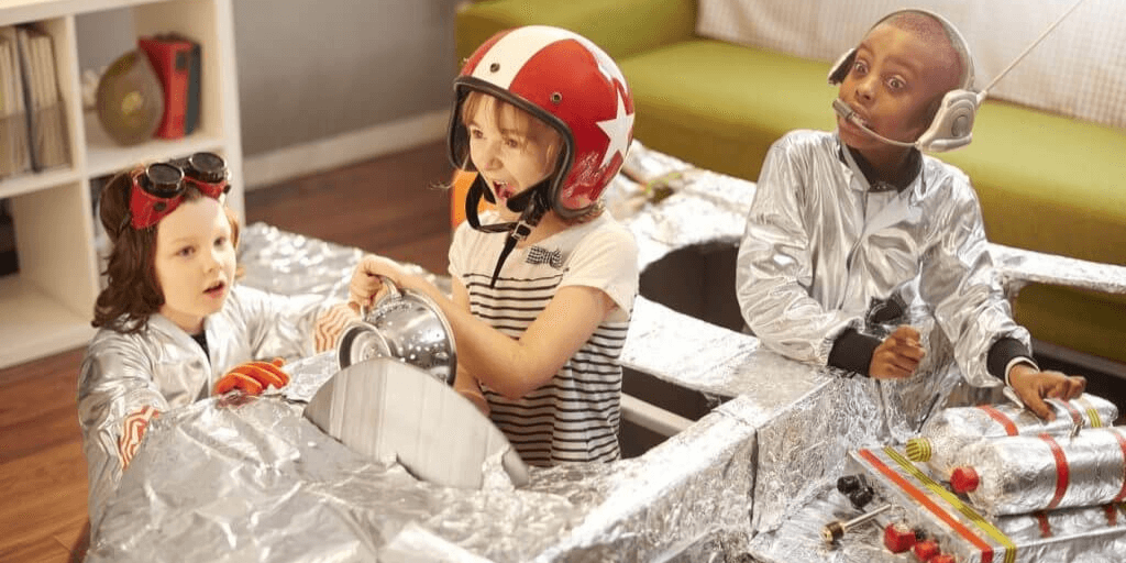 Young kids aspiring to become astronauts playing with cardboard boxes made into rocket ships