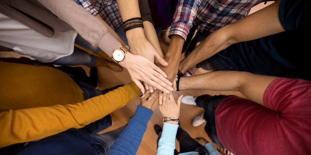 A group of employees holding hands together, showing workplace diversity.