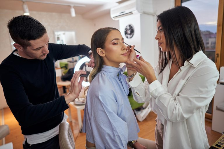 A young woman in a salon getting her makeup and hair done by professionals in the makeup industry