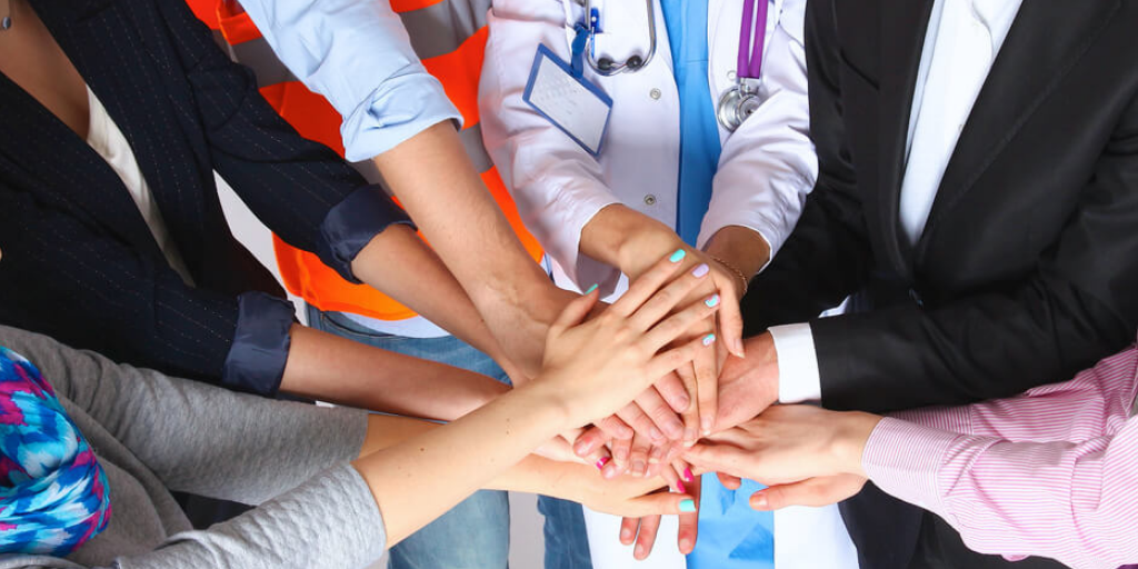 A diverse group of public health workers and their hands together.