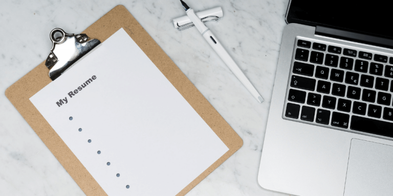 resume tips in a notebook next to a macbook