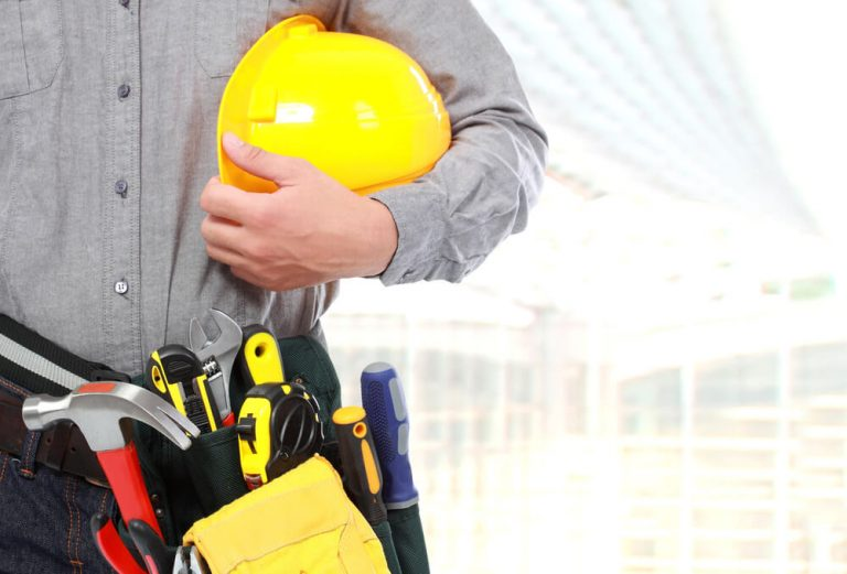 Essential worker holding safety hat and equipment.