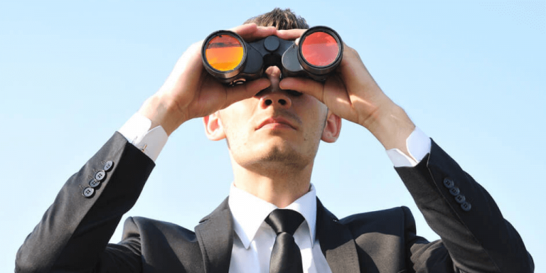 A man with binoculars on the search for top jobs.