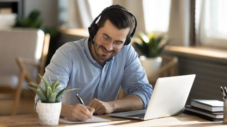 A man with headphones working happily at his desk.